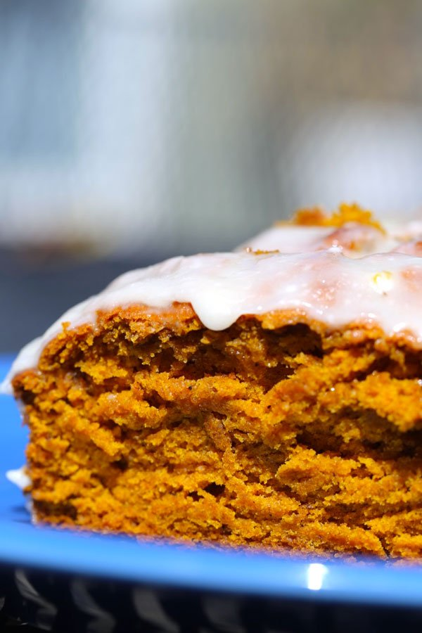 Close up of moist pumpkin bread slice on a blue plate.