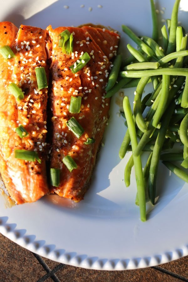 Honey garlic salmon on a white plate with a side of green beans.