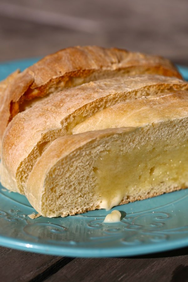 Slices of homemade french bread on a blue plate.