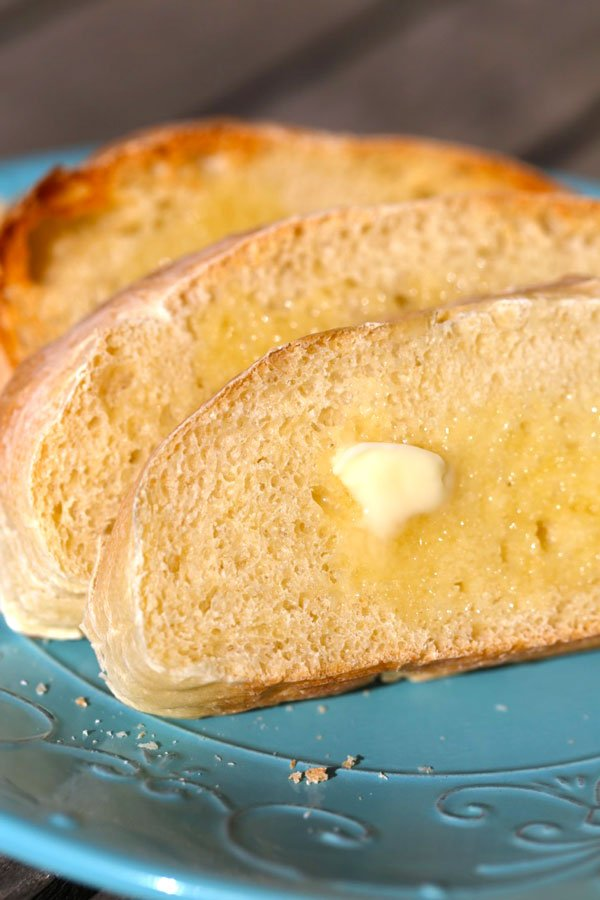 Slices of homemade french bread with melting butter on a blue plate.