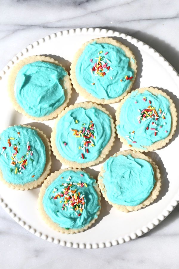 Cookies with aqua frosting on white plate.