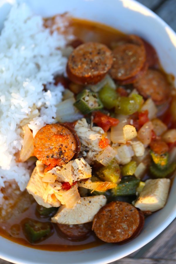 Chicken sausage gumbo in white bowl with rice.