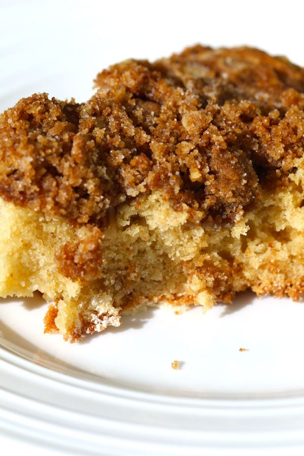 Slice of cinnamon coffee cake on white plate.