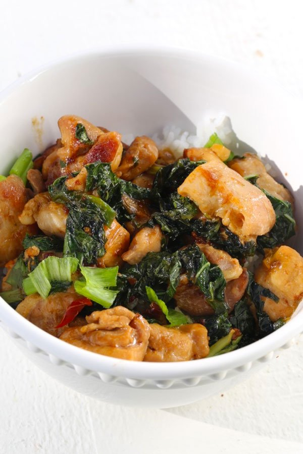 White bowl with chicken and basil stir fry.