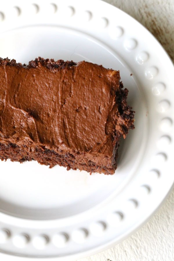 Slice of chocolate cake with thick chocolate frosting on white plate.