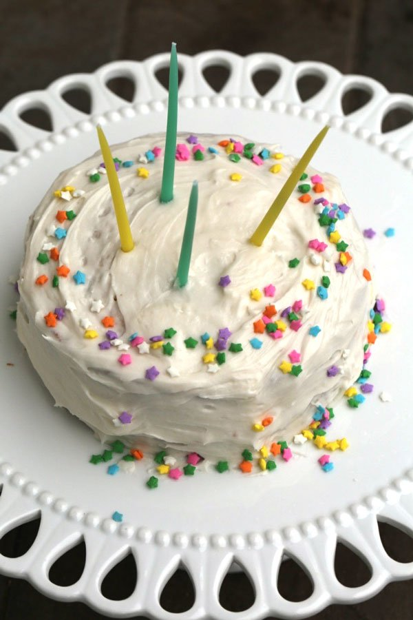 Small cake with confetti sprinkles on white platter.