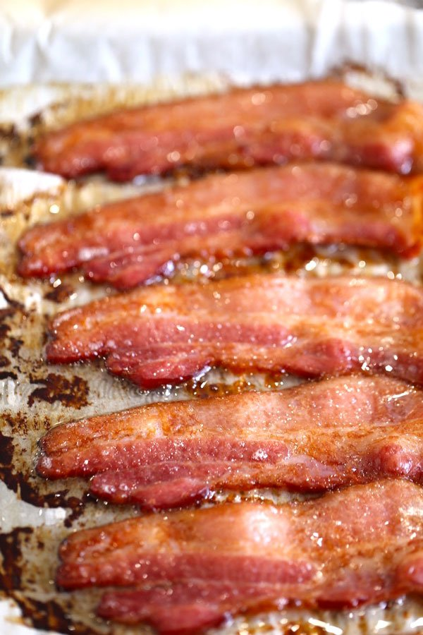 Sizzling bacon cooked in the oven on foil just after being removed from oven.
