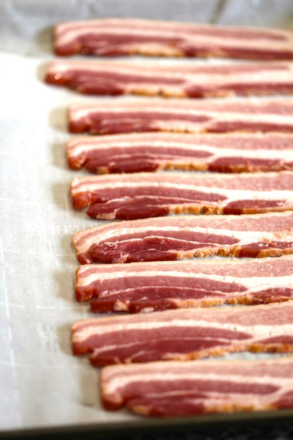 Raw bacon on parchment paper prepared for cooking in the oven.