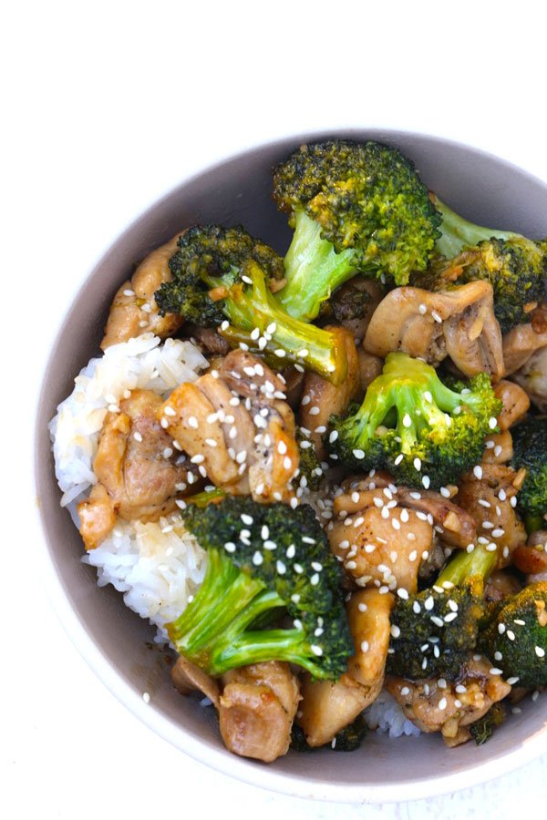 Chicken Broccoli Stir Fry on top of rice in a brown bowl.