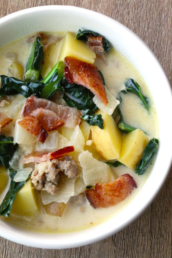 Sausage Potato Soup in a white bowl with Kale and bacon.