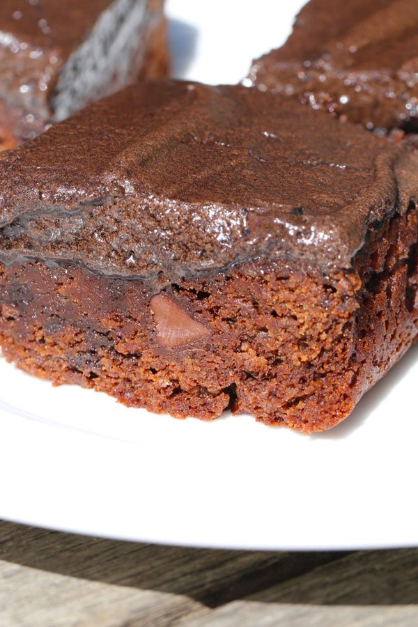 Chocolate chip brownies with frosting on a plate.