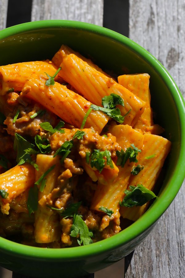 Rigatoni and sausage with tomato cream sauce in green bowl