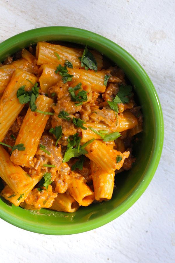 Rigatoni and Sausage with tomato cream sauce in a green bowl