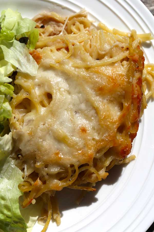 Cheesy Chicken Tetrazzini with a side salad on a plate.