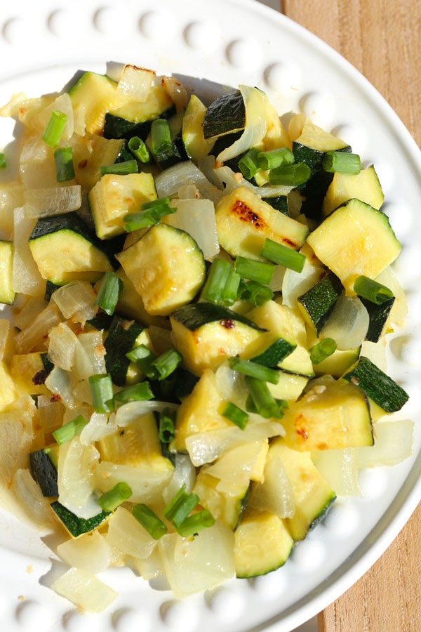 Sauteed zucchini and onions on a white plate.
