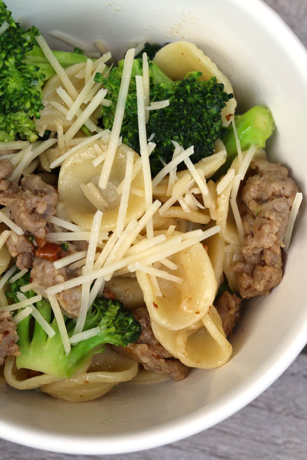 Italian sausage pasta with broccoli in a white bowl.