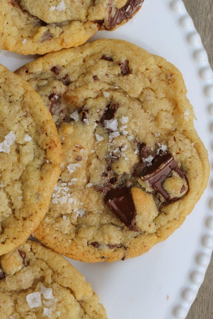 Brown butter sea salt chocolate chip cookies on a white dessert plate.